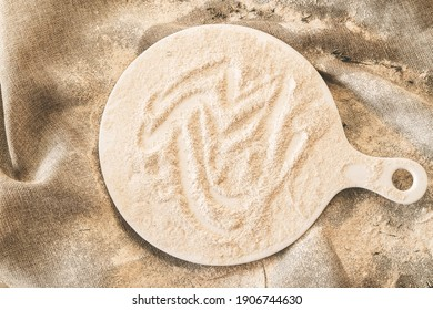 Baking background, heap of flour on wood with copy space. Wooden board on white
