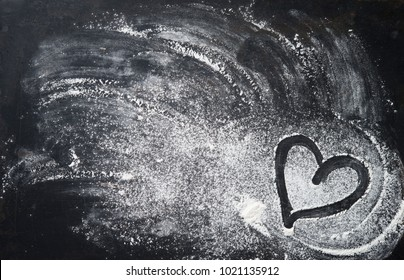 Baking background with heart shape and flour on the dark table. Copy space for text