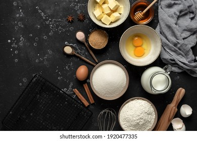 Baking background. Baking ingredients: flour, eggs, sugar, butter, milk and spices on black stone background. Top view