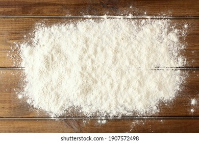 Baking background with white flour on rustic wooden table. Baker workplace with flour