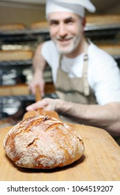 Baking bread. A handsome baker with a loaf of fresh bread standing in the bakery.