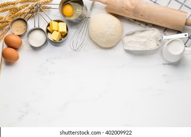 Baking cake, dough recipe ingredients (eggs, flour, milk, butter, sugar) on white table.