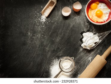 Baking cake ingredients. Bowl, flour, eggs, egg whites foam, eggbeater, rolling pin and eggshells on black chalkboard from above. Cooking course poster background - layout with free text space.