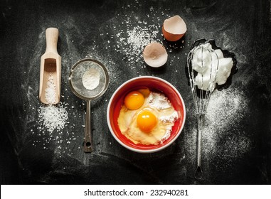 Baking cake ingredients - bowl, flour, eggs, egg whites foam, eggbeater and eggshells on black chalkboard from above. Cooking course or kitchen mess poster concept.