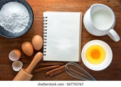 Backzutaten, Kochbuch, Schüssel, Mehl, Eier, Eiweißschaum, Eierbecher, Walzstift und Eierschalen auf Holztisch