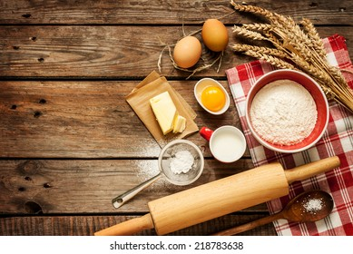 Baking cake in rural kitchen - dough recipe ingredients (eggs, flour, milk, butter, sugar) on vintage wooden table from above. Background layout with free text space.