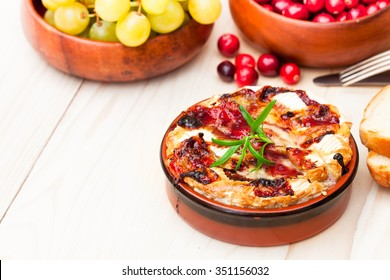 baking  camembert with cranberry sauce and rosemary served with toasted bread and grapes