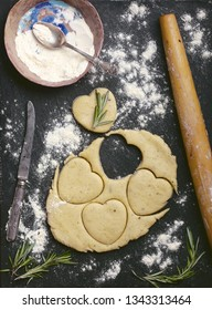 baking cheese cookies recipe photo of empty food background with cookies heart shape cut out of dough, rolling pin, flour, rosemary and vintage knife on slate stone surface. copy space for text