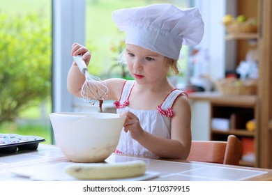 Baking with children: little happy kid, adorable toddler girl in white chef hat helping mother to prepare delicious pastry in the kitchen, bowl, flour, butter and banana muffins