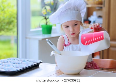 Baking with children. Little happy kid, adorable toddler girl in white chef hat adding flour to the bowl with dough ingredients helping mother to prepare delicious pastry in the kitchen