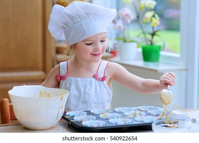 Baking with children: little happy kid, adorable toddler girl in white chef hat filling cupcakes form with dough ingredients helping mother to prepare delicious pastry in the kitchen
