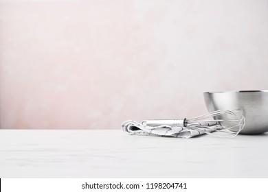 Baking concept. Bowl with a whisk and dishcloth on white marble table over pink background with copy space.
