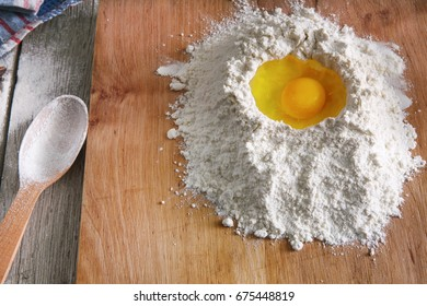 Baking concept. Flour and eggs on rustic wooden table, cooking ingredients. Making dough