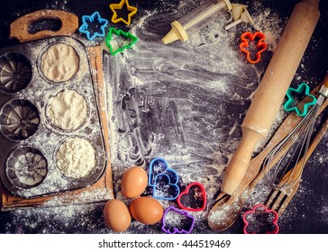 Baking concept on dark background. Baking cookies for children, top view of variety of baking utensils with different kind of flour, eggs and colorful cutters on black chalkboard. Top view.