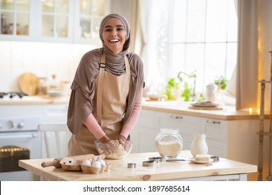 Baking Concept. Portrait Of Joyful Muslim Woman In Hijab Kneading Dough In Kitchen Interior, Cheerful Islamic Female In Hijab And Apron Having Fun While Preparing Homemade Pastry, Laughing At Camera