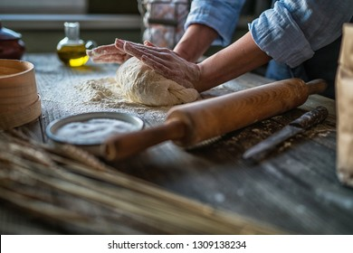 Baking concept. Working woman prepares pastry by himself, kneads dough on wooden counter with flour and rolling pin. Female cook bakes bread or delicious bun.