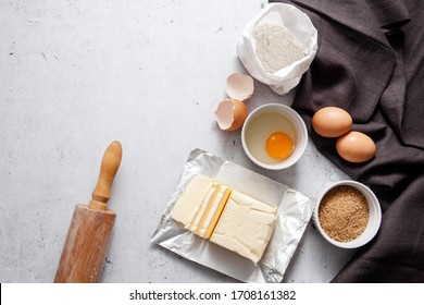 Baking cooking ingredients: a bag of flour, eggs, egg with  yolk in a bowl,  brown sugar, butter dark linen cloth, rolling pin, on light grey concrete background. Top View Copy Space.  Recipe Mockup