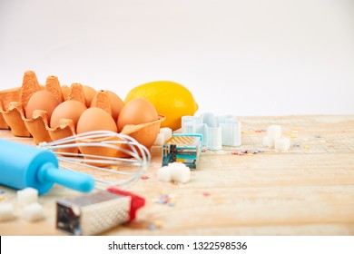 Baking or cooking ingredients - flour, eggs, lemon,  sugar,  and different tools on a wooden table background.  Dessert ingredients and utensils.  Bakery frame. Top view, copy space. Fla
