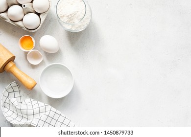 Backen Kochzutaten Mehl Eier Rollpinkbutter und Küchen Textilien auf hellgrauem Betonhintergrund. Kopienraum oben anzeigen Cookies Pie oder Cake Recipe Mock up