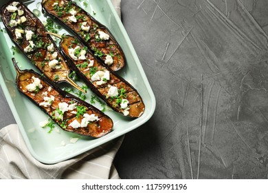 Baking dish with fried eggplant slices on grey background, top view. Space for text