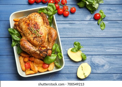 Baking dish with golden roasted turkey and vegetables on wooden background