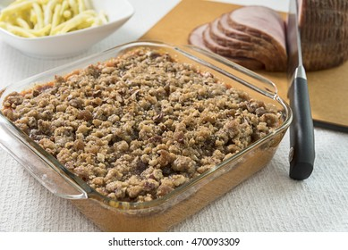 Baking dish of streusel topped sweet potato casserole, with a cutting board of sliced ham, and bowl of fresh yellow string beans in the background