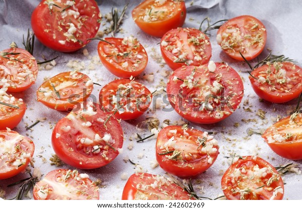 baking dish of tomatoes seasoned with garlic spices and sugar for the preparation of confit tomatoes
