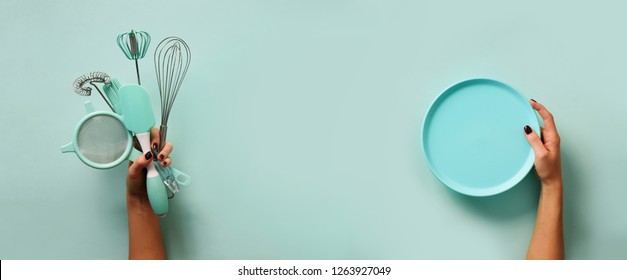 Baking flat lay. Female hands holding plate, kitchen tools, sieve, rolling pin, spatula and bruch on pastel blue background. Banner with copy space.