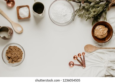 Baking flat lay on a white backdrop with peanut butter, flour, and winter greenery.