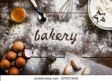 Baking flatlay with kitchen utensils, flour, eggs and the word bakery written in flour in the center on a dark wooden background. Cooking stylized background. Rural background. Ingredients, kitchen it