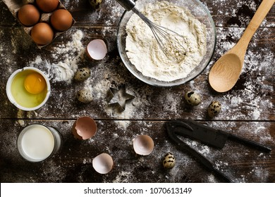 Baking flatlay with kitchen utensils, flour and eggs on a dark wooden background. Cooking stylized background. Rural background. Ingredients, kitchen items for baking cakes.Chaos, disorder.