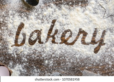 Baking flatlay with the word bakery written in flour in the center on a dark wooden background. Cooking stylized background. Rural background.