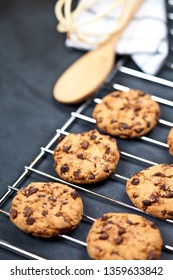 Baking grid with chokolate cookies on blackboard background and kitchen utensil.