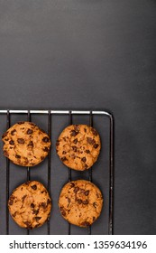 Baking grid with chokolate cookies on blackboard background. Top view with copy space.