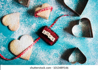 Baking Heart Shaped Cookies for valentine's day, with the words love created with colored stamps,  over an azul background,top view