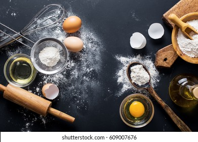 Baking ingredients. Bowl, eggs, flour, eggbeater, rolling pin and eggshells on black chalkboard from above.
