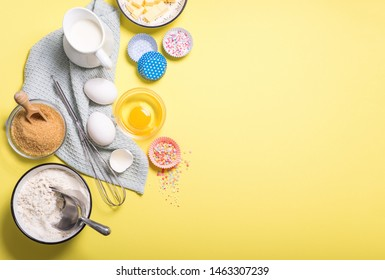 Baking ingredients for cake, cupcakes or muffins on yellow copy space background, eggs, sugar, flour, milk for dough and whisk, place for text