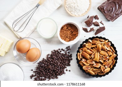 baking ingredients with chocolate and pecan nut for sweet pastry on white wooden table