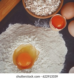 Baking ingredients for cooking. Eggs, pile of flour, oatmeal and milk over dark background.
