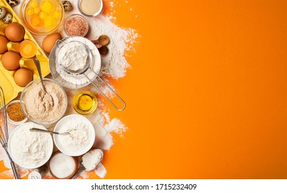 Baking ingredients for dough on yellow color background, top view of flour, eggs, butter, sugar and kitchen utensils for homemade baking. Cooking concept banner with copy space for text