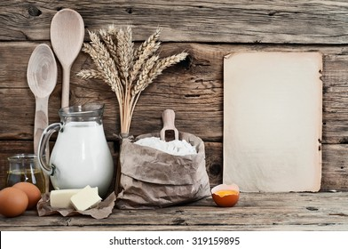 Baking ingredients eggs, flour, milk, butter, sunflower oil on wooden background with a blank sheet. Top view. Free space for text. Food background