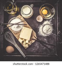 Baking ingredients eggs, flour, sugar, butter, vanilla, cream