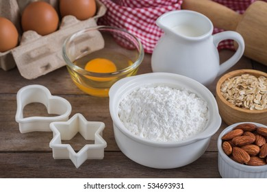 Baking ingredients flour, egg, milk, almonds, oat on wooden table