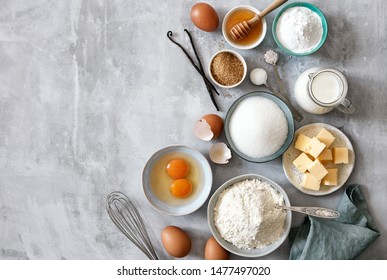 Baking ingredients: flour, eggs, sugar, butter, milk and spices on gray marble background. Top view. Space for text