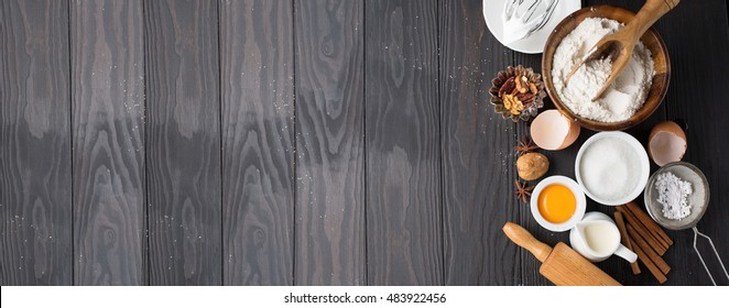Baking ingredients for homemade pastry on dark rustic wooden background. Bake sweet cake dessert concept. Top view, Long web format