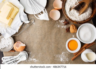 Baking ingredients for homemade pastry on dark rustic wooden background. Bake sweet cake dessert concept. Top view, flat lay style