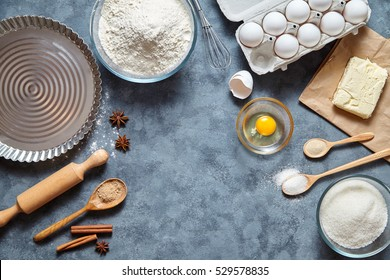 Baking ingredients for homemade pastry on dark background. Bake sweet cake dessert concept. Top view, flat lay style