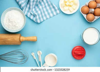 Baking ingredients on blue background. Rolling pin, flour, eggs, butter, measuring spoons and other cooking baking ingredients for cake, pastry or cookies. Top view with copy space