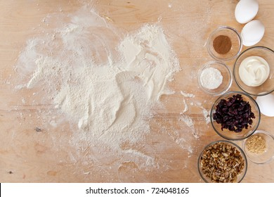 Baking ingredients on kitchen table. Products for filling cupcakes prepare for cooking on wooden cutting board. Overhead lifestyle food concept with copy space.