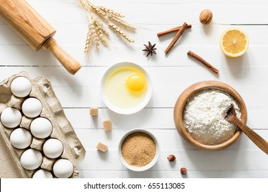 Baking ingredients on white table. Box of white eggs, brown sugar, spices, lemon, white flour and rolling pin on white wooden table background. Top view